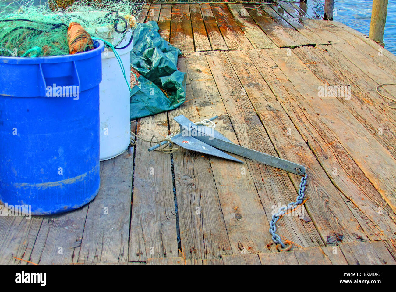 Anchor on a Dock with Plastic Barrels Holding Fishing Nets - Stock Image