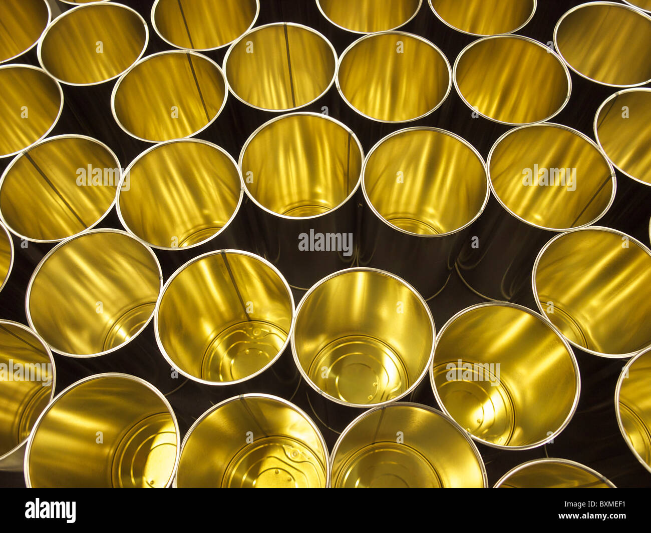 Empty cans on production line in a factory, ready to be filled. - Stock Image