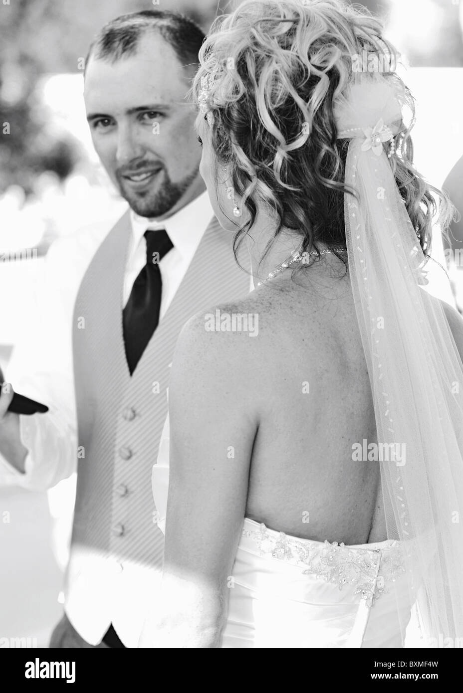 candid photo of groom standing behind bride during toast at