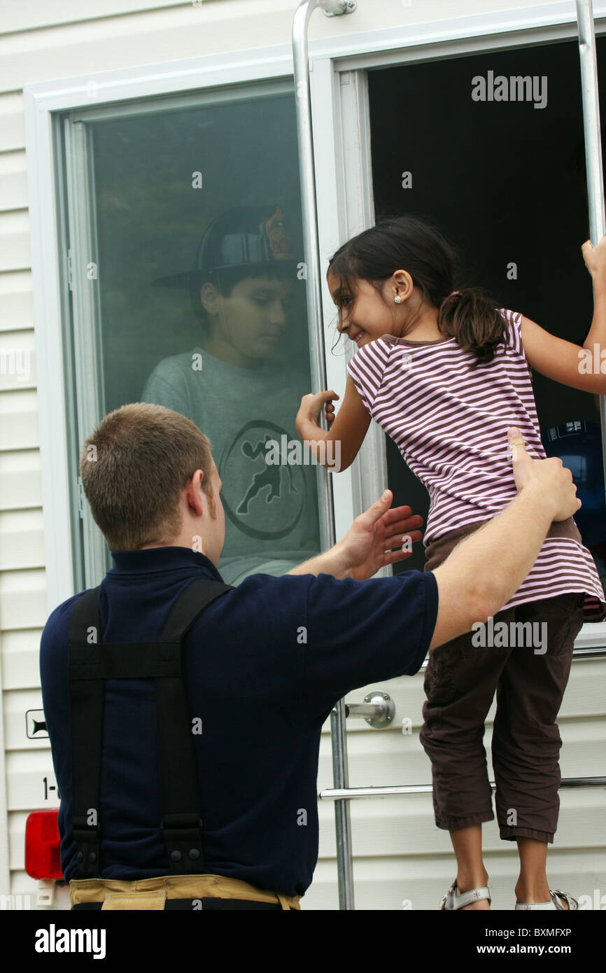 A firefighter guiding a child exiting the fire Safe House showing home fire safety - Stock Image