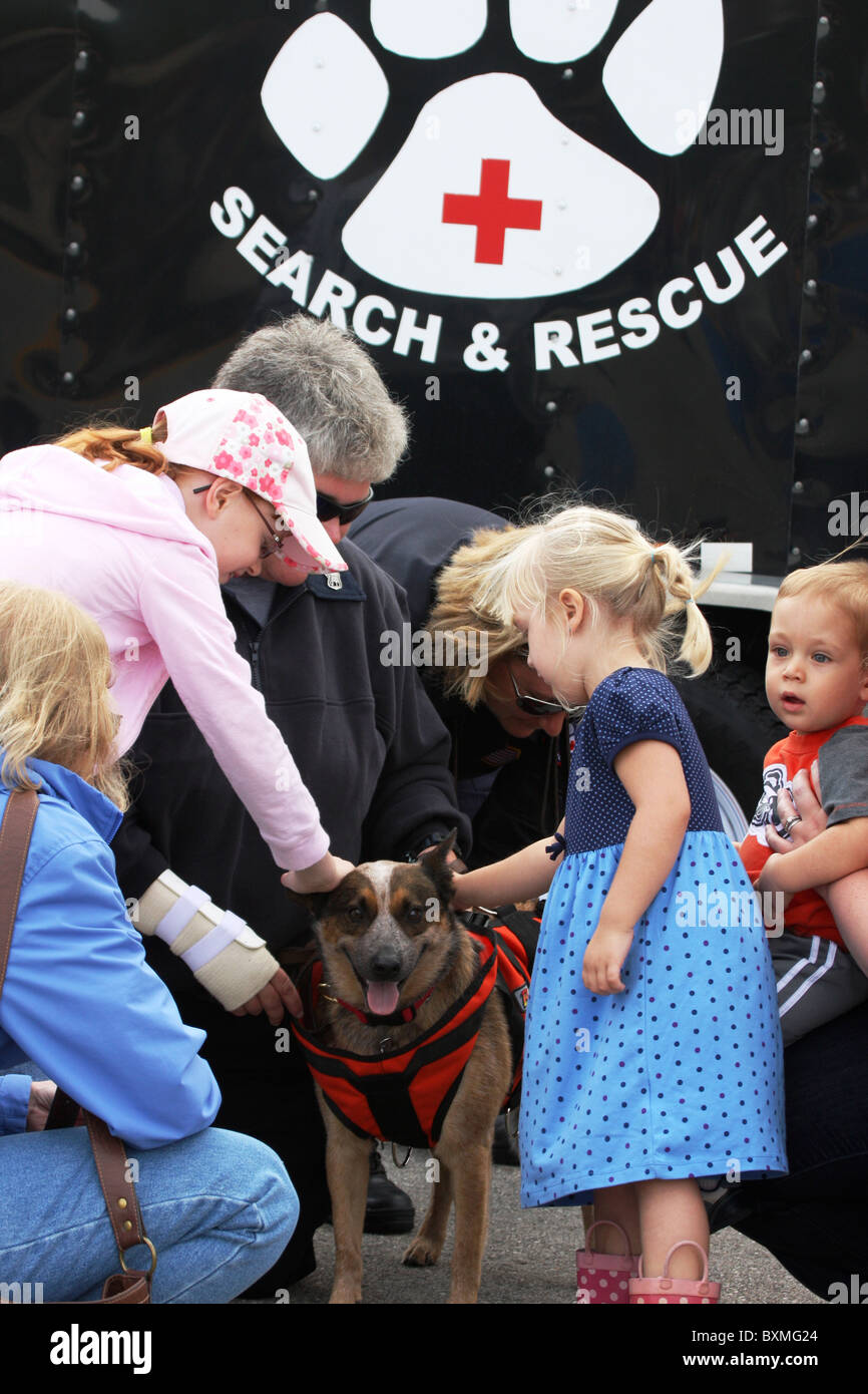 Search and Rescue dog being petted by young children at a safety fair - Stock Image