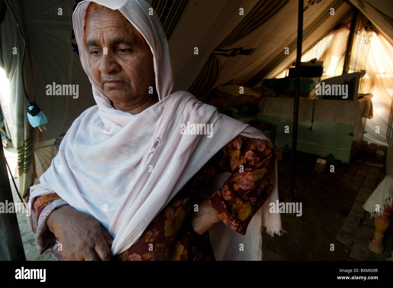 Pakistan after the flood. Woman living in a tent since her house was damaged by the flood - Stock Image