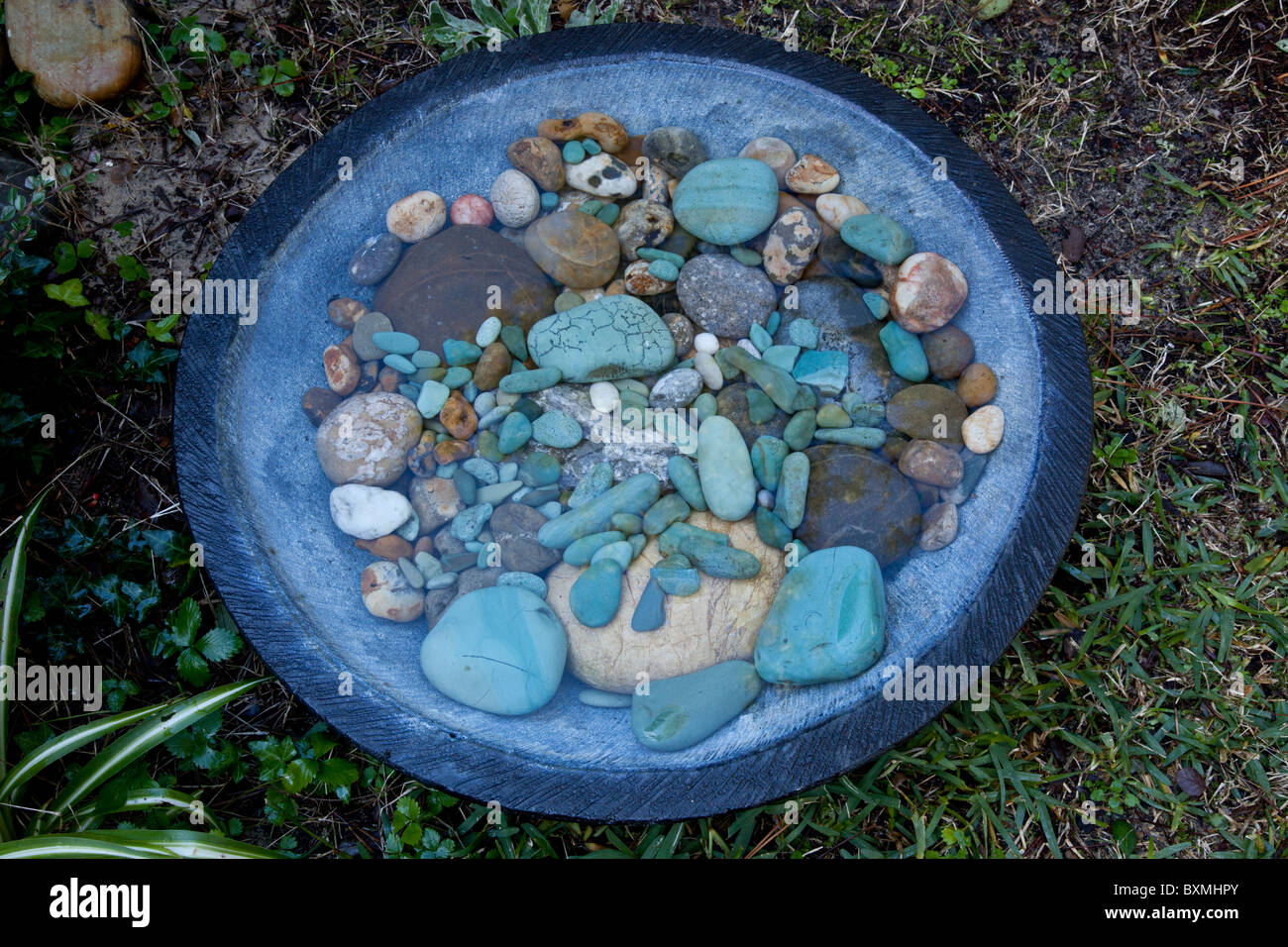 A Balinese cast stone concrete round bowl filled with multicoloured pebbles. Vasque Balinaise ronde et galets multicolores. - Stock Image