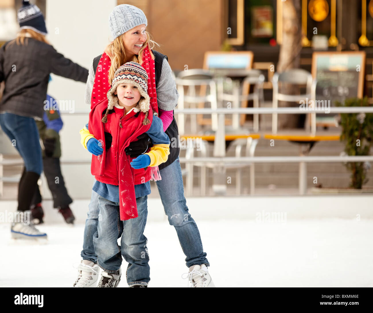 a mother helps her son learn to ice-skate - Stock Image