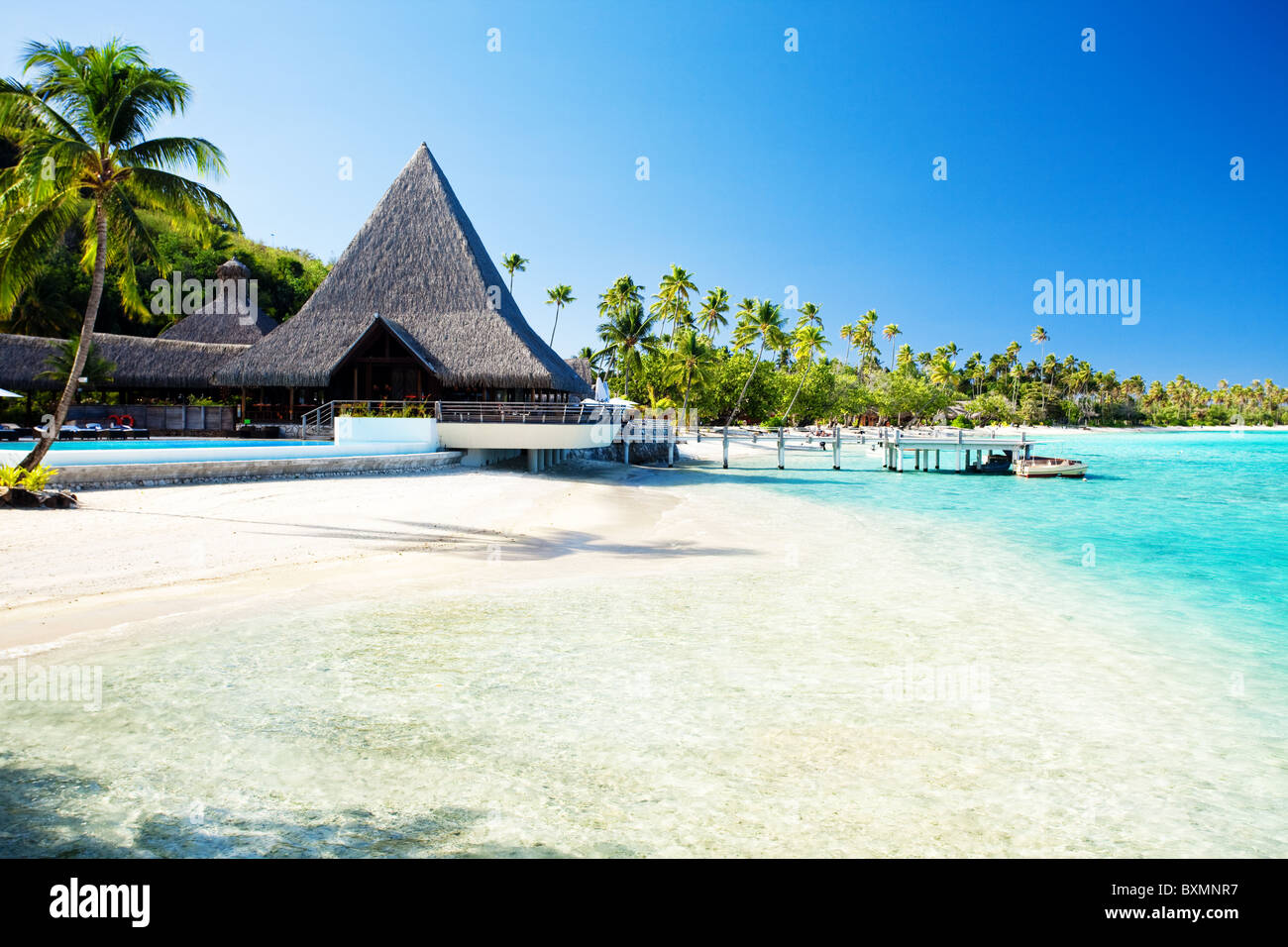 Little jetty and boat on tropical beach with amazing water - Stock Image