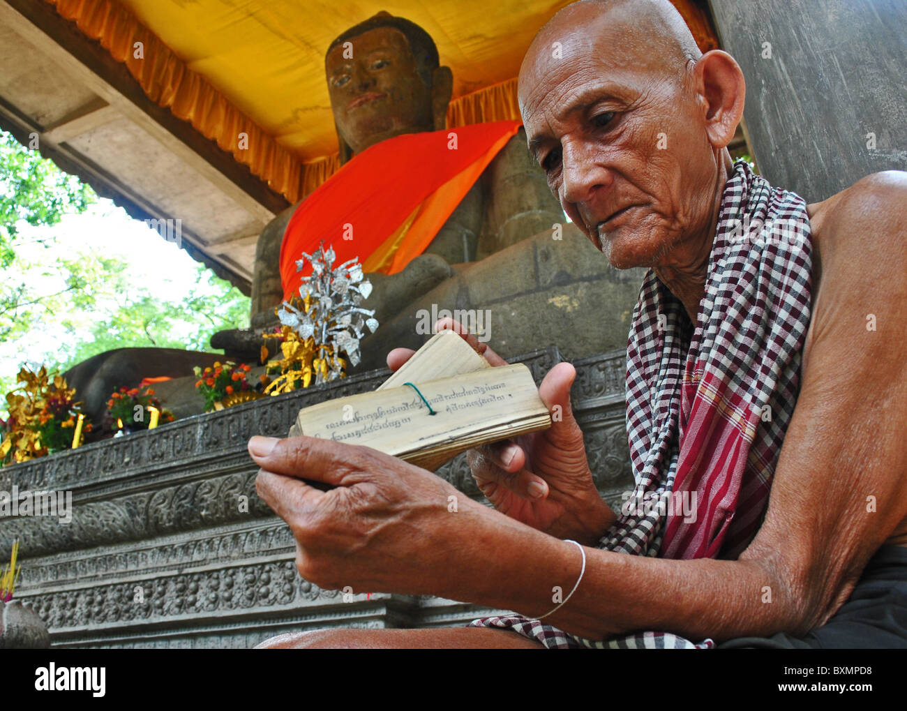 Old Buddhist monk reading scripts at a temple near Angkor Thom, Cambodia - Stock Image