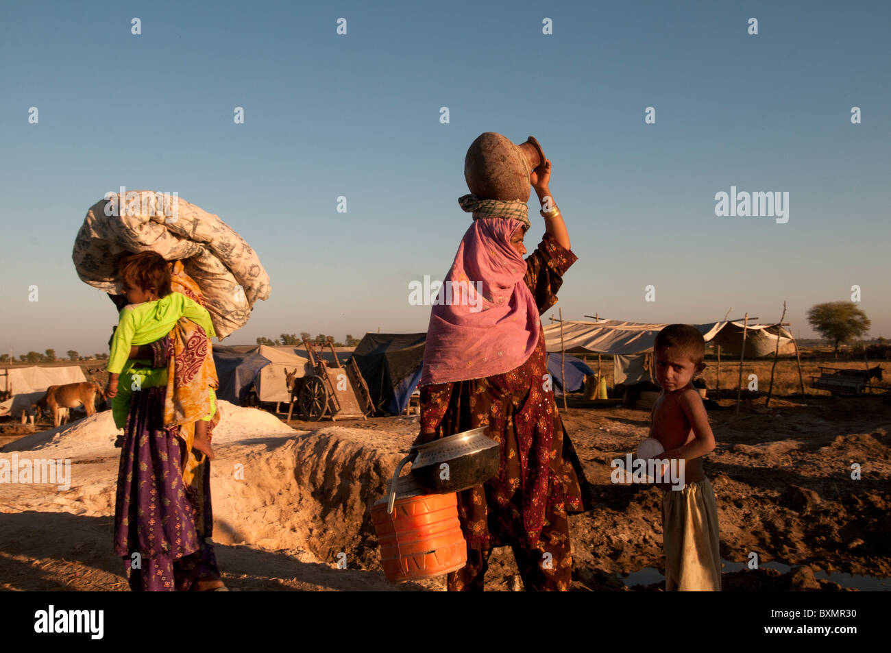Sindh province Shaddat Kot .After the flood. Petrol station camp for displaced people.Two women walking with their - Stock Image