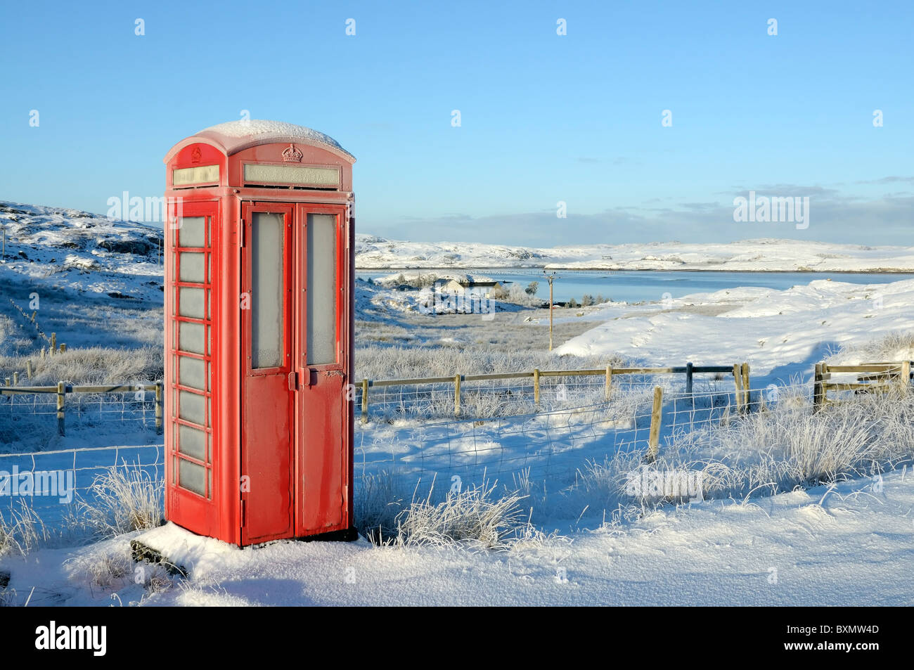 Old style red UK phone box in a rural setting in snow - Stock Image