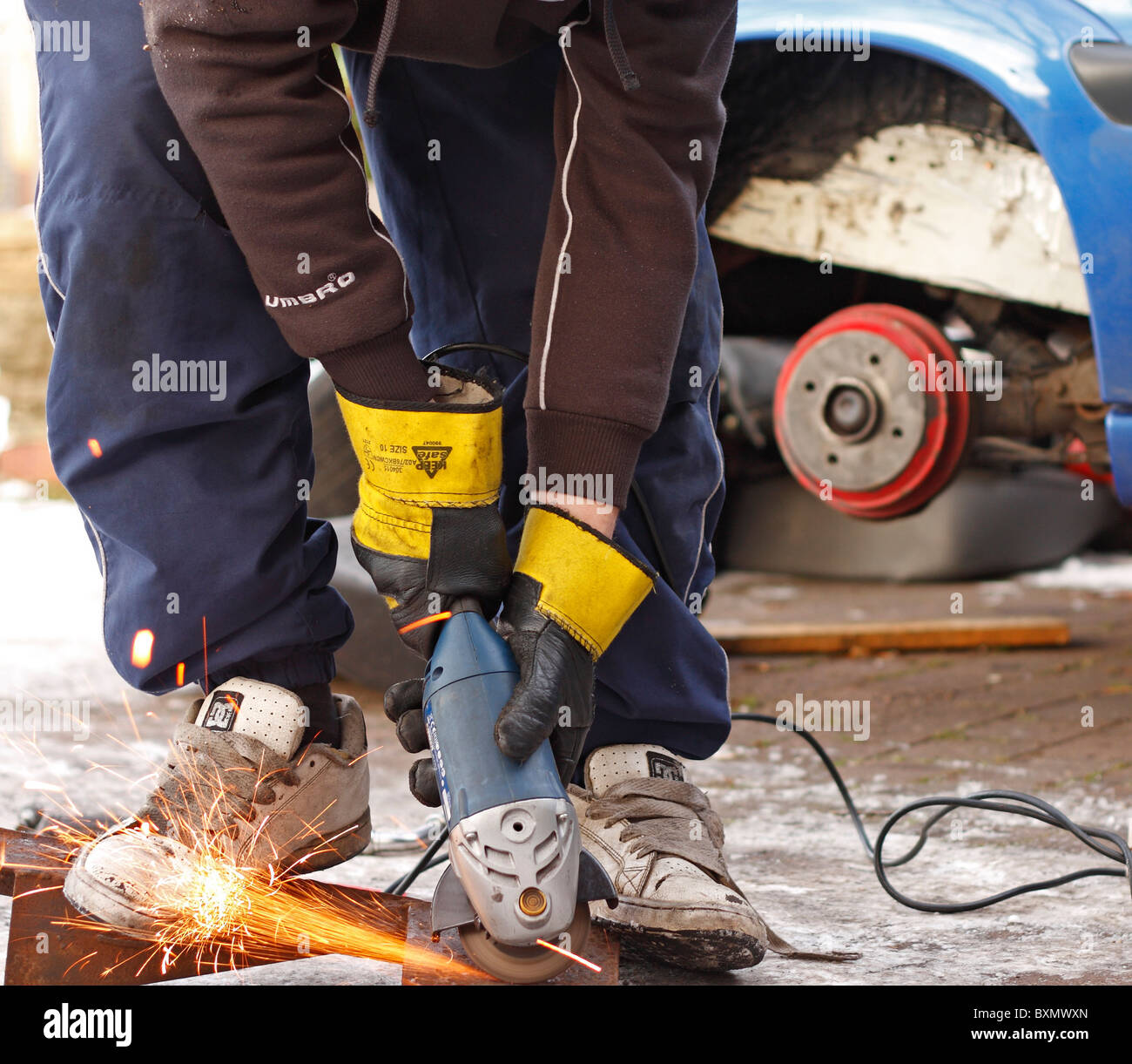A teenage male using an angle grinder whilst working on repairing the chassis of a car, wearing protective gloves. - Stock Image