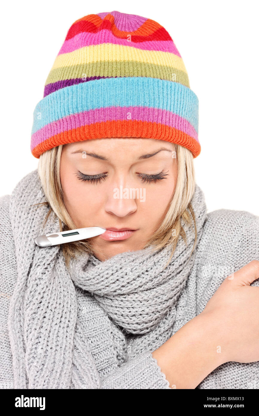 Ill woman wearing a cap and scarf with thermometer in her mouth - Stock Image