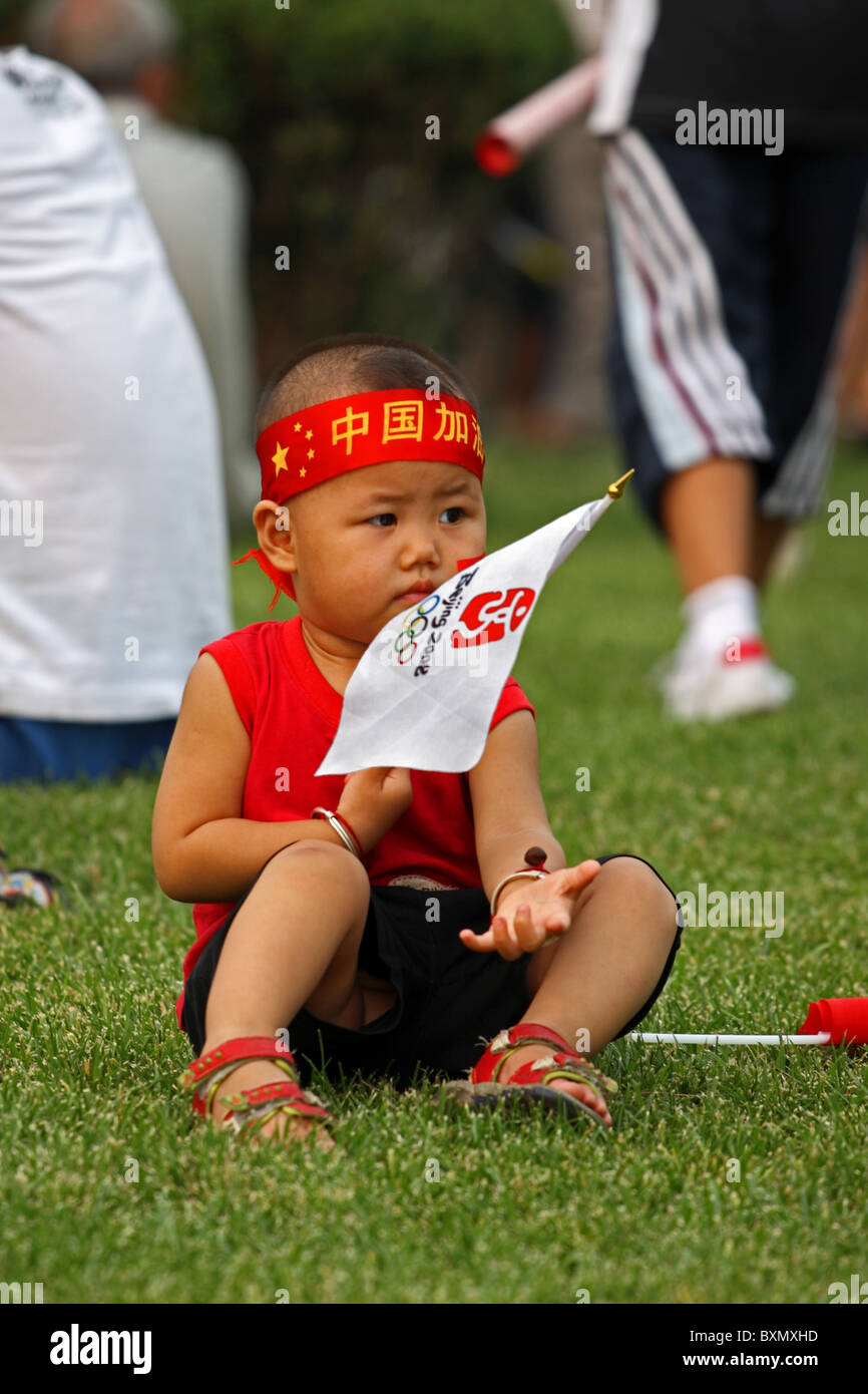 Chinese child sits playing with Olympic Games flag, Beijing, China - Stock Image