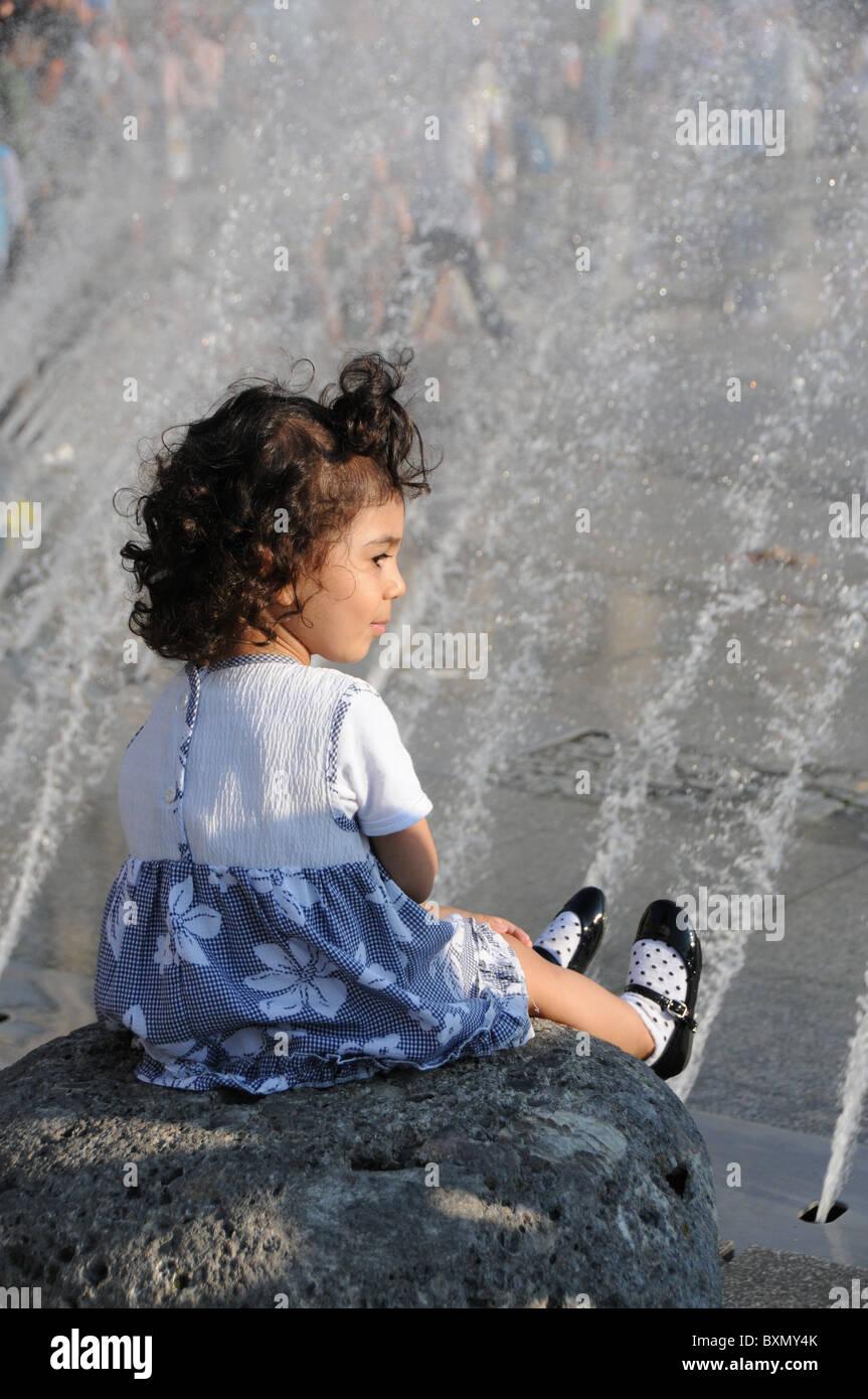 Girl sitting at the Karlplatz fountain in Munich - Stock Image