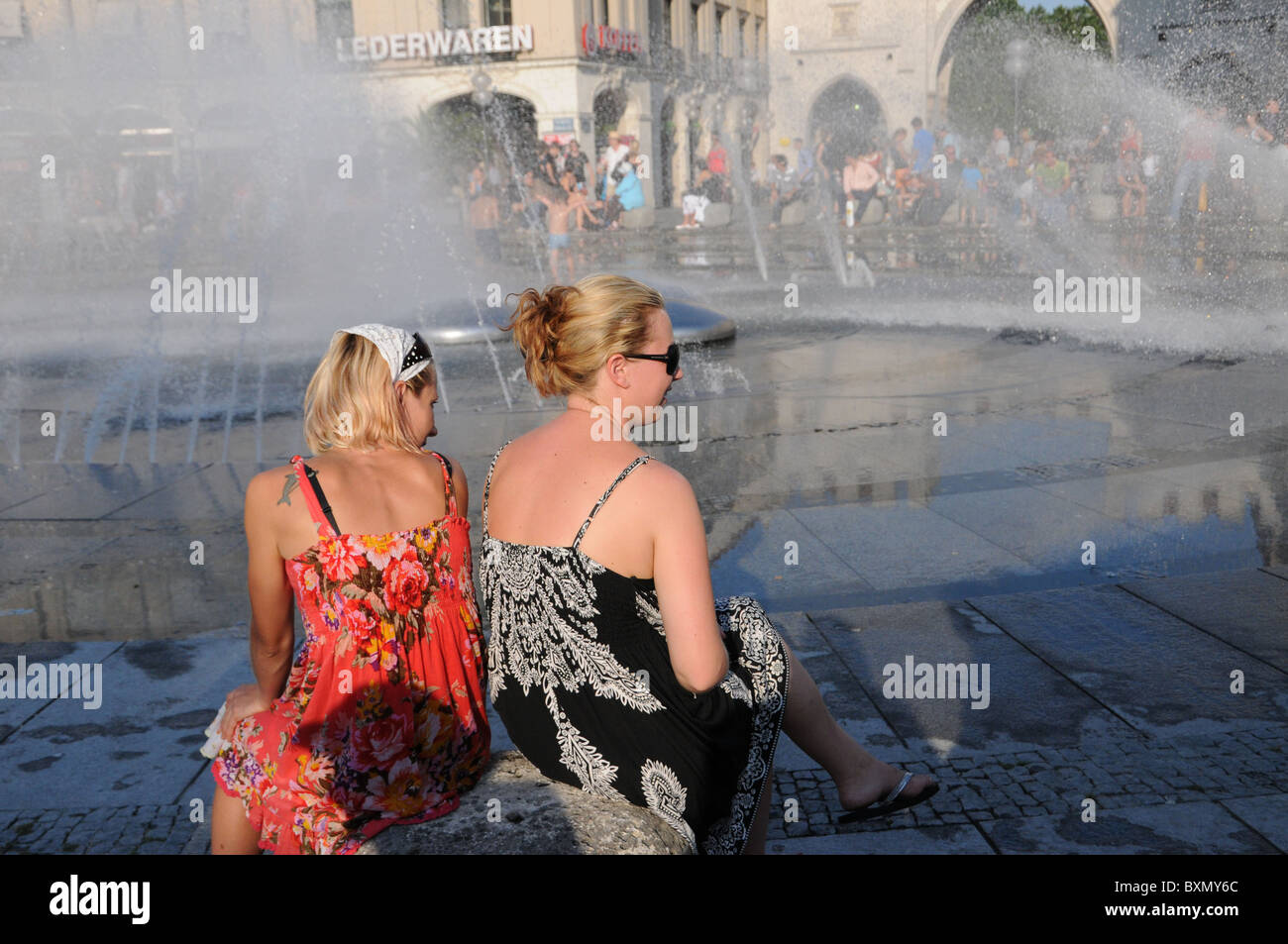Two woman sitting at the Karlsplatz Fountaine in Munich - Stock Image
