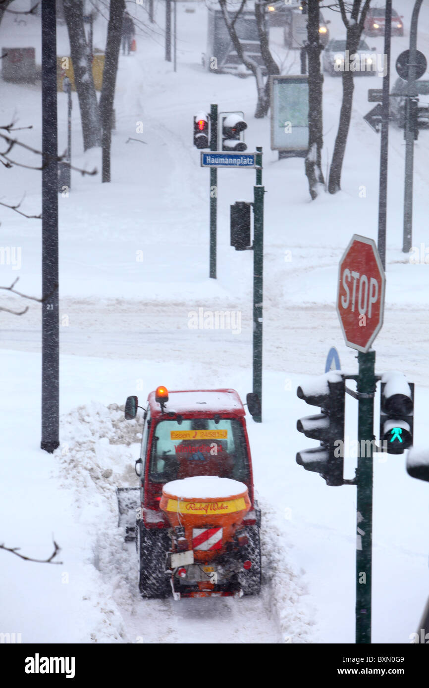 Wintertime, traffic in a city center, snow covered streets. Street and walkway cleaning, snowplough in action. - Stock Image