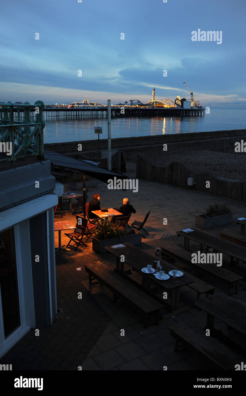 Couple sitting at seafront cafe bar at dusk by the Palace Pier in Brighton at dusk Stock Photo