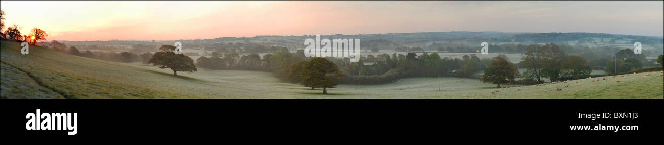 A panoramic photo of the sun ricing on a cold and frosty morning - Stock Image