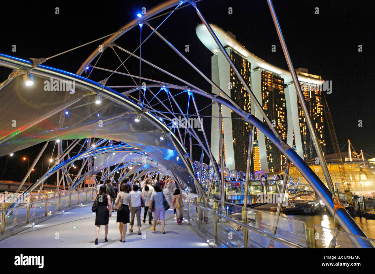 Singapore: The Helix Bridge at night with Marina Bay Sands Resort Hotel and Shopping Mall in the backgrounnd - Stock Image