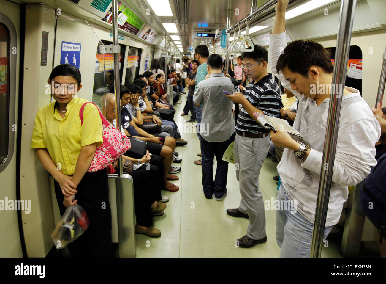 Singapore: Passengers in a car of MRT (Mass Rapid Transport) subway train system - Stock Image