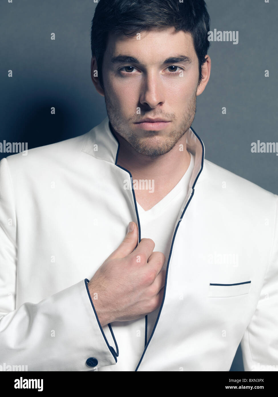 Fashion photo of a young smiling man wearing a white blazer - Stock Image