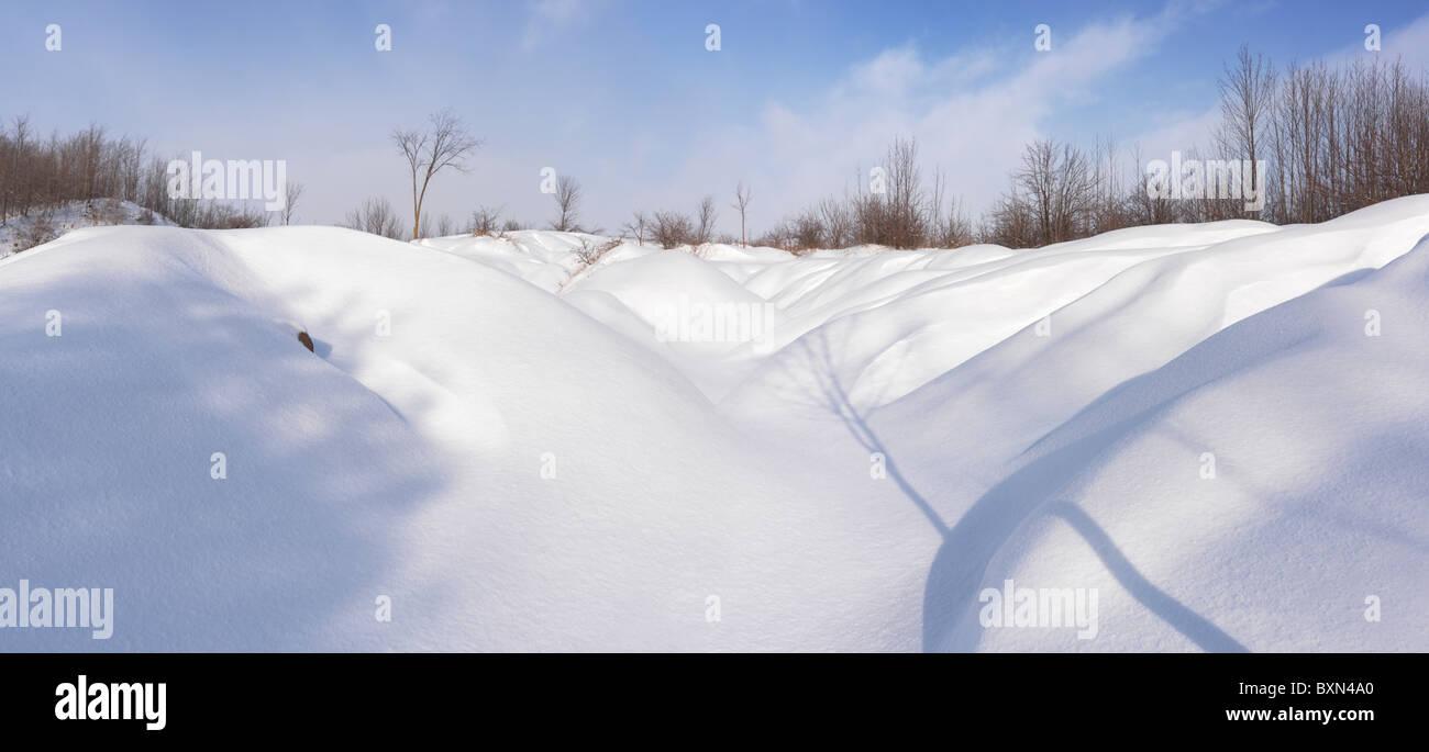 Snow dunes under blue sky. Wintertime panoramic scenery. Ontario, Canada. - Stock Image