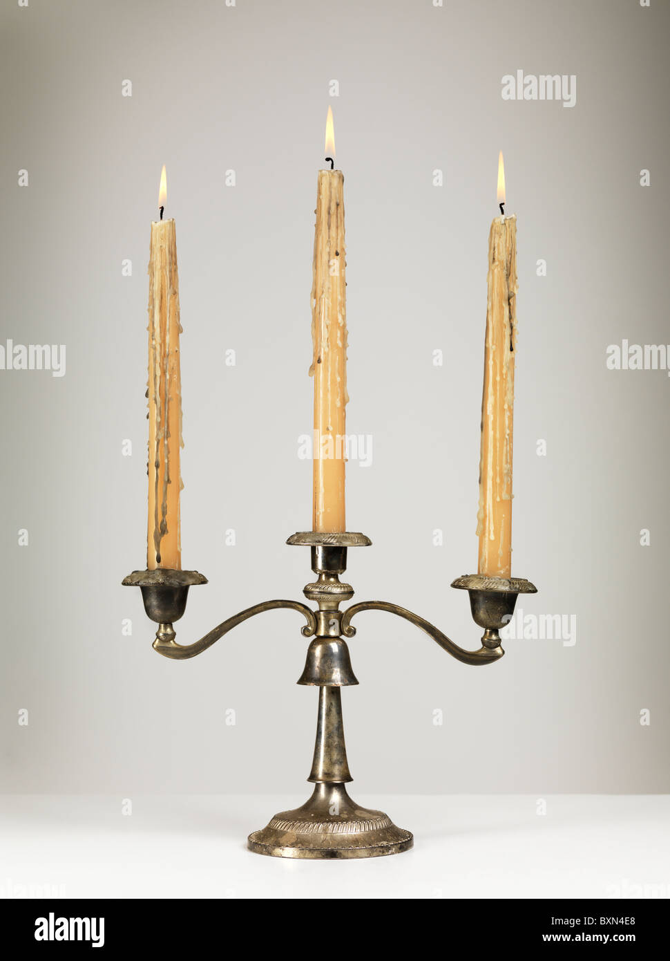 Antique silver triple candle holder candelabra isolated on gray background - Stock Image