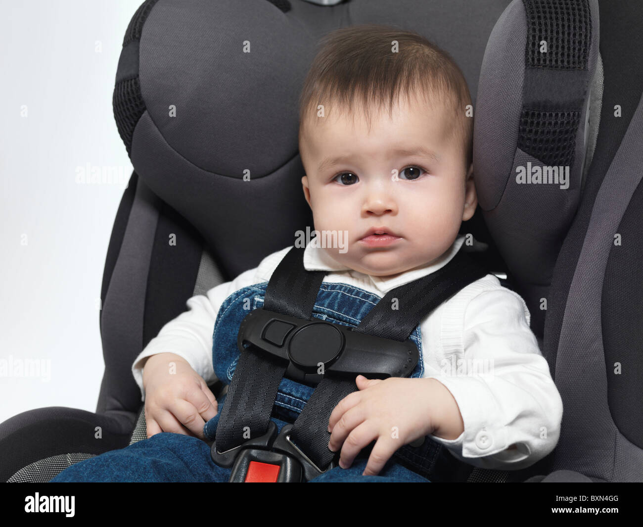 Seven month old baby sitting in a booster seat - Stock Image
