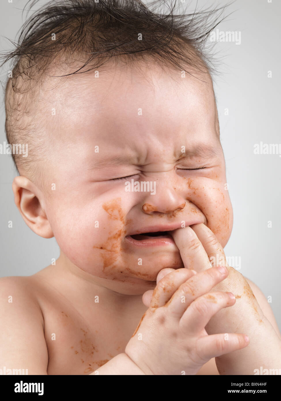 Artistic portrait of a crying seven month old baby boy with messy hair and smudged with food face Stock Photo