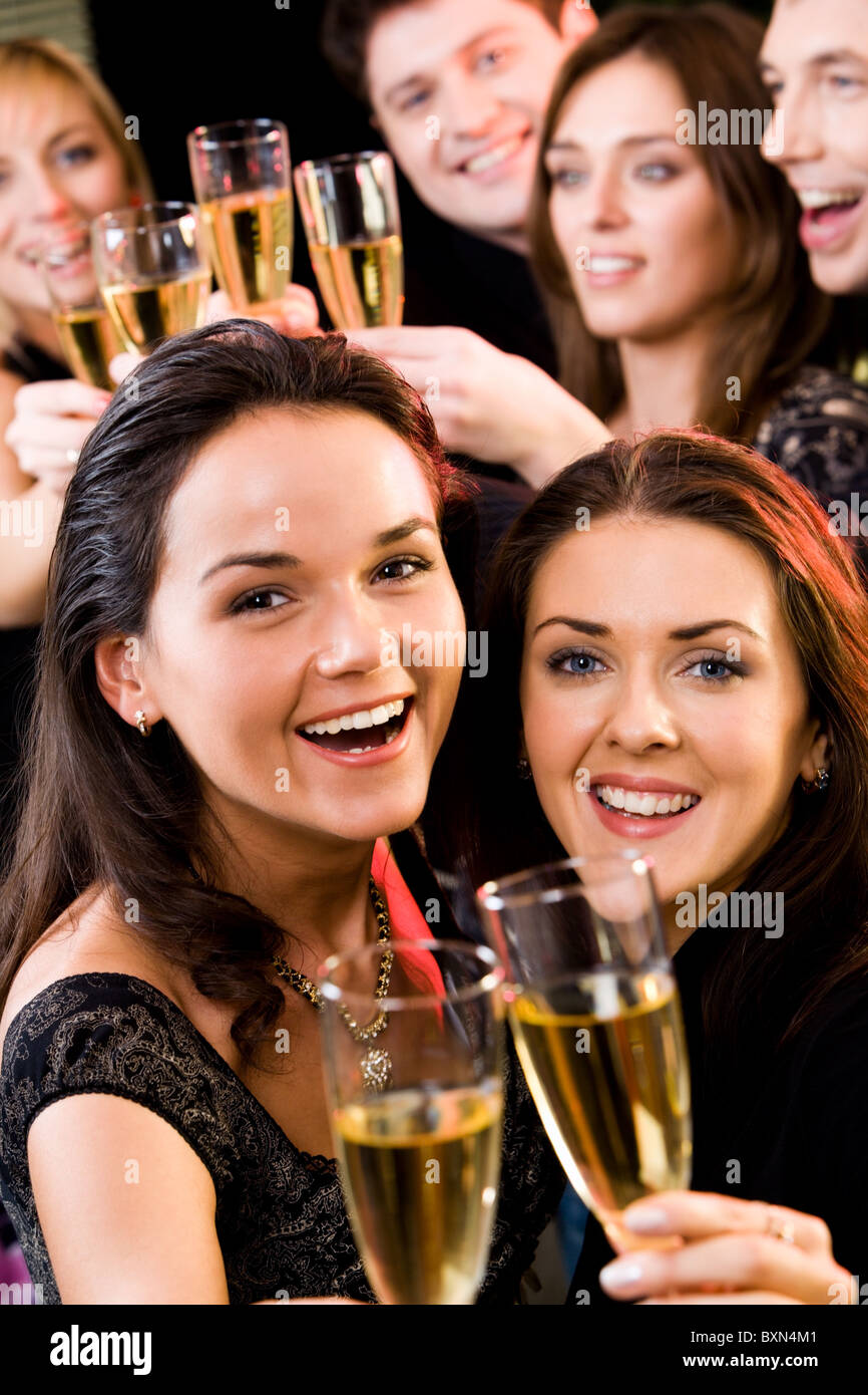 Two young charming women clink glasses at a evening-party - Stock Image