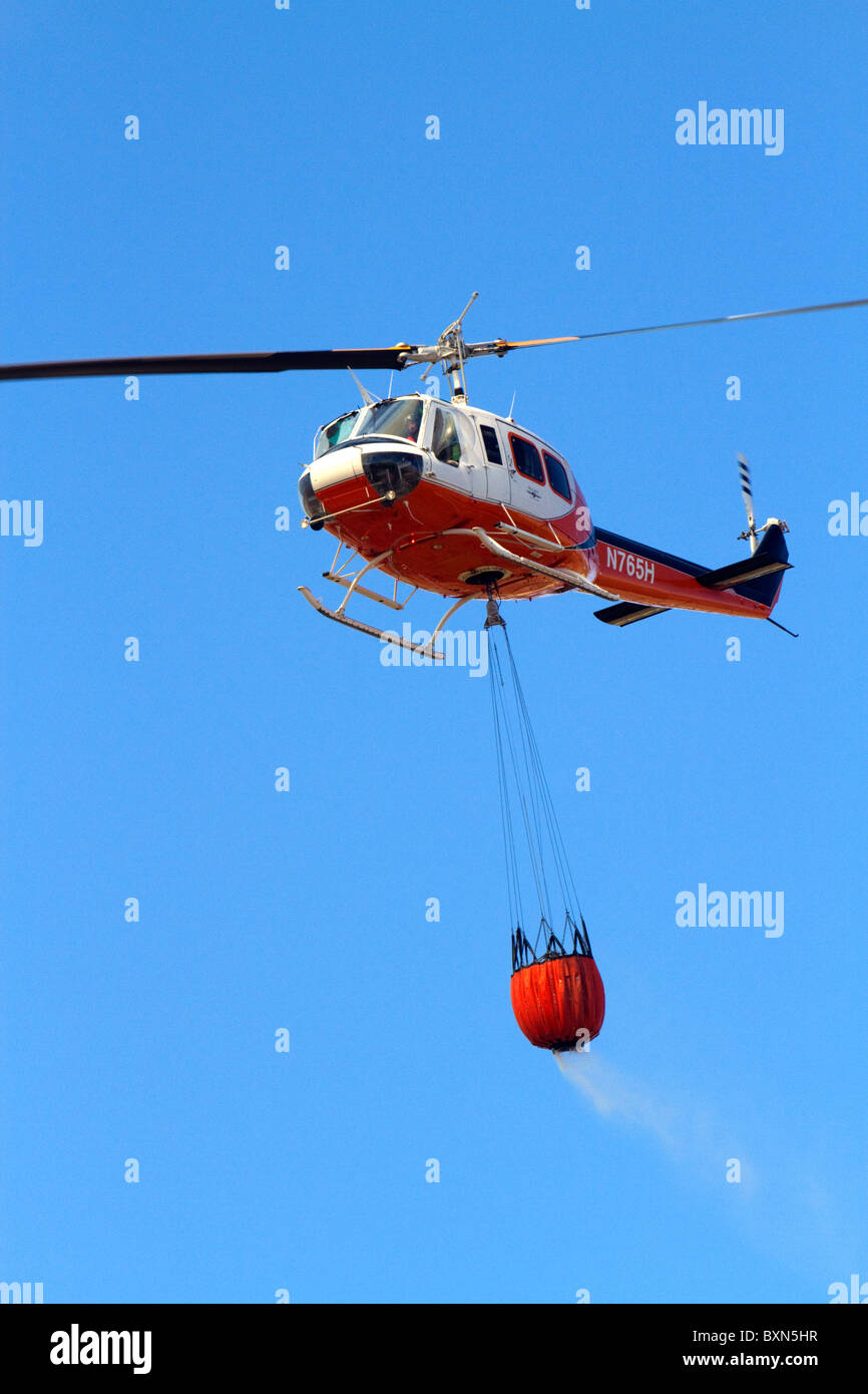 Helicopter with water bucket performing aerial firefighting on a wildfire near Boise, Idaho, USA. - Stock Image