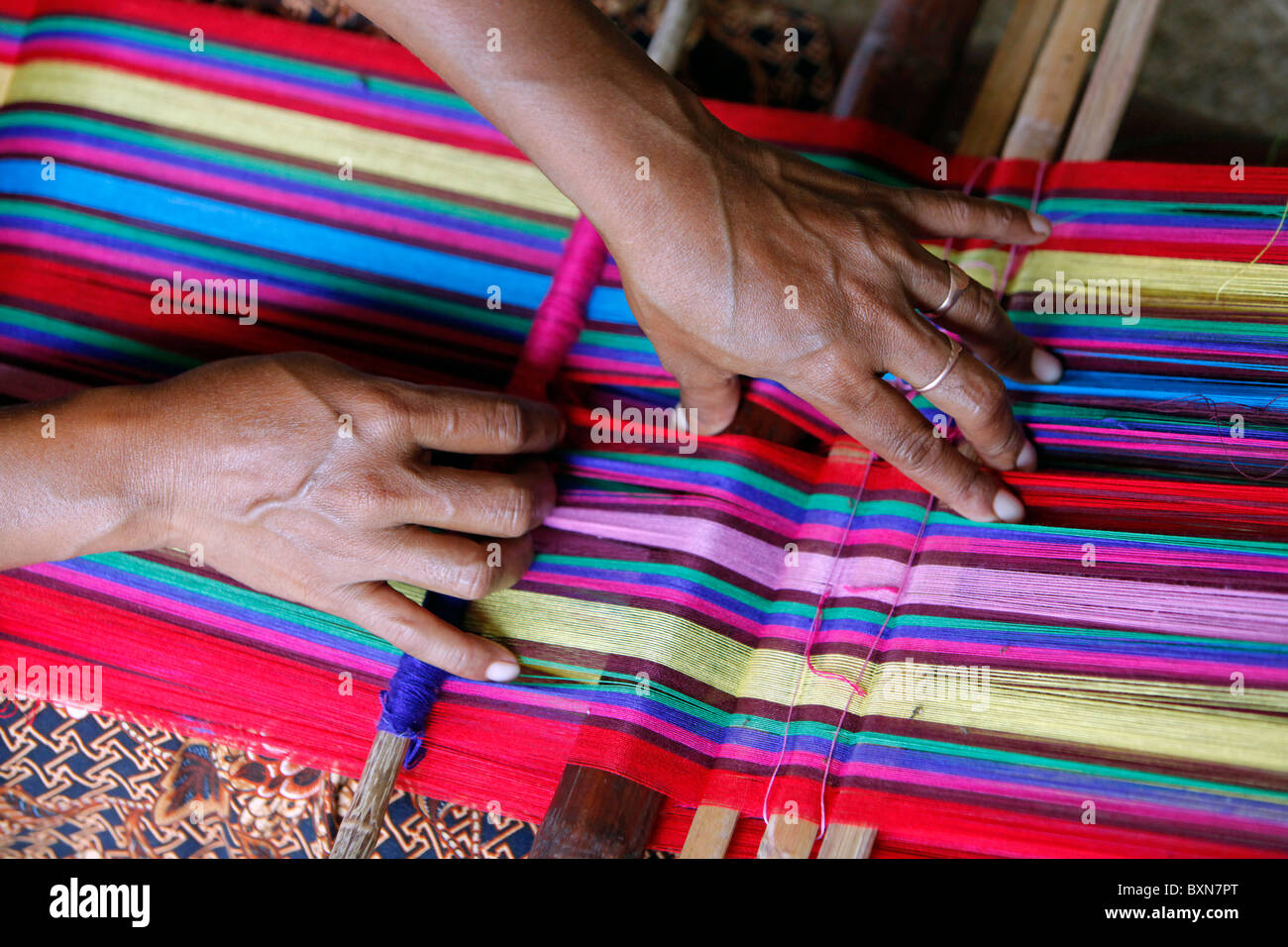 Woman traditionally weaving tais on backstrap loom in Timor Leste (East Timor) - Stock Image