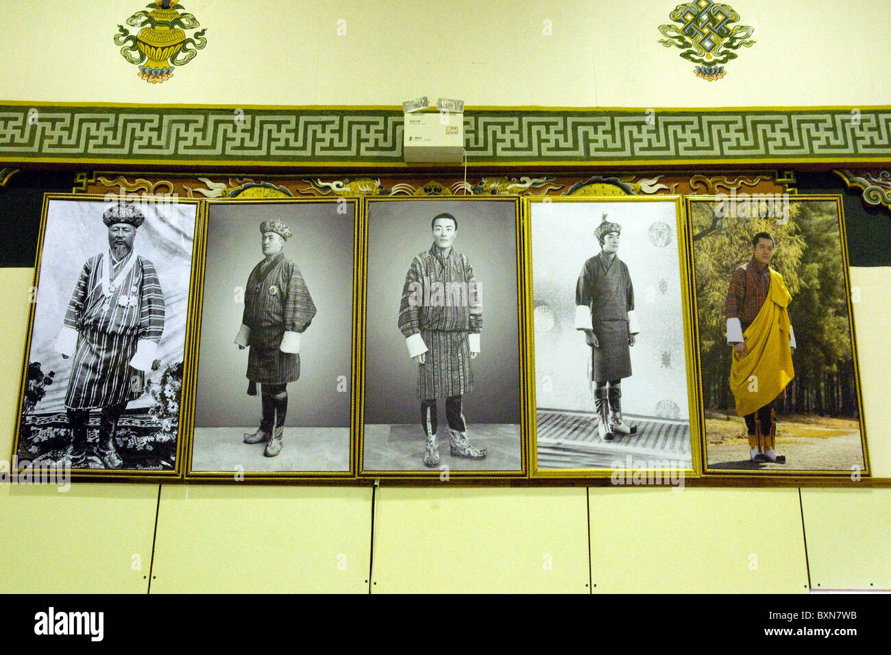 On an airport wall the five kings of Bhutan--the current, far right, His Majesty Jigme Khesar Mangyel Wangchuck - Stock Image