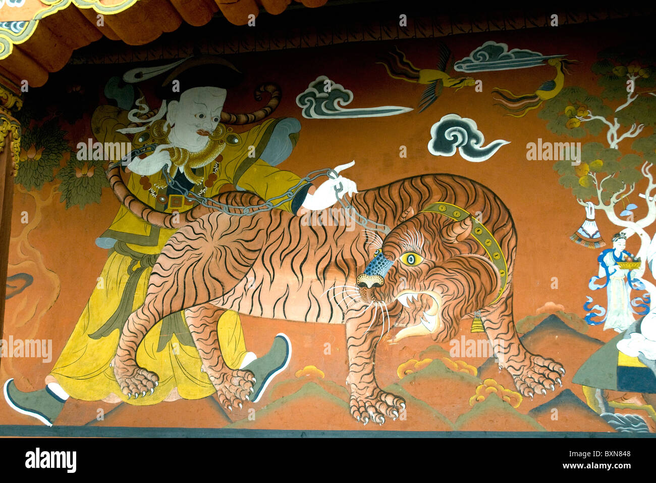 The sacred legend of Guru Rinpoche and a flying tiger painted on a wall of the Paro dzong (or administration fortress) - Stock Image