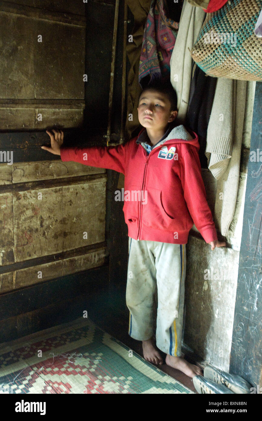 A small boy stands barefoot in the corner of his family's farmhouse near Paro in Bhutan - Stock Image