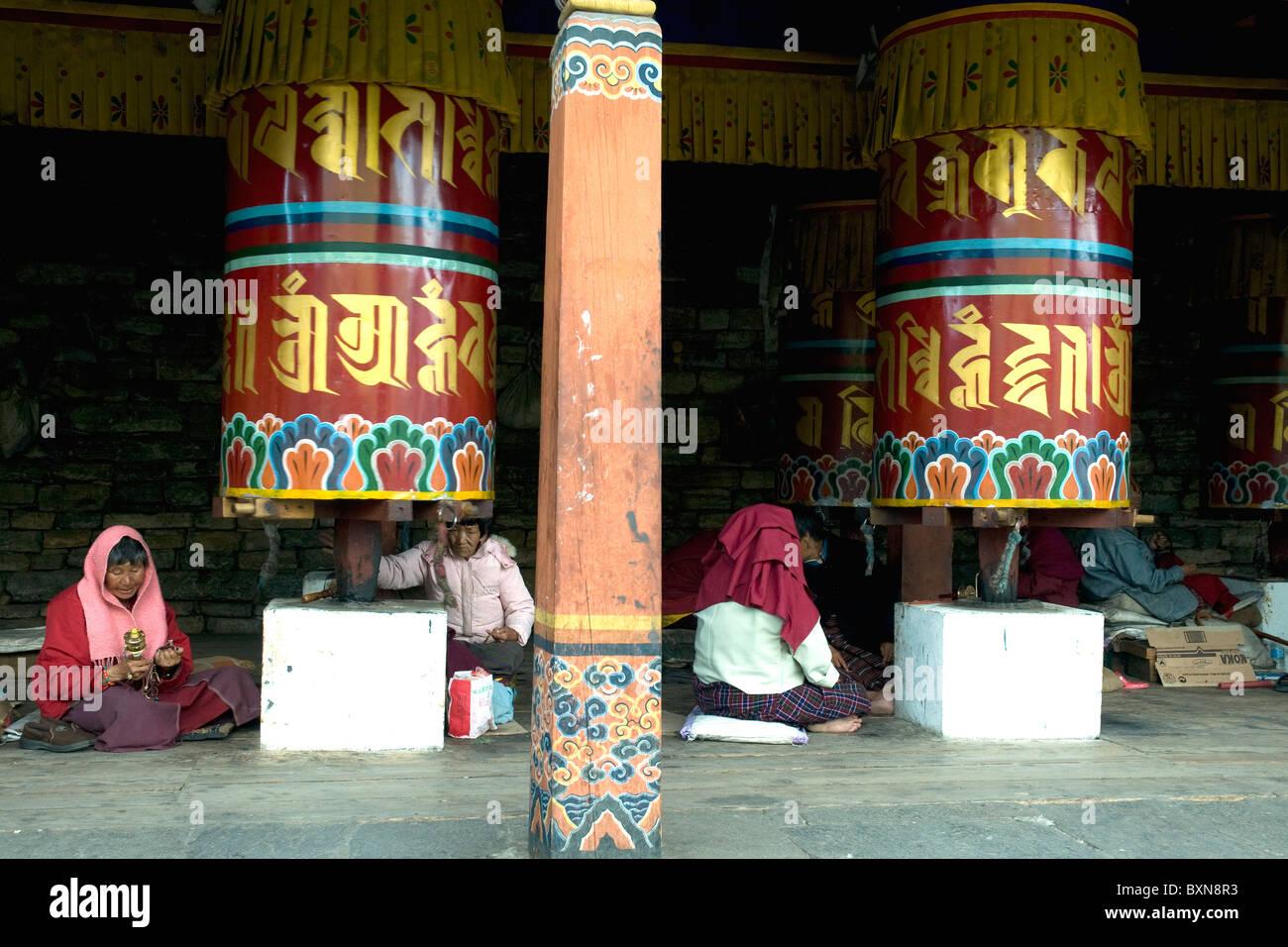Pilgrims resting beside large prayer wheels at the Kyichu Lakh Buddhist temple near Thimpu in Bhutan - Stock Image
