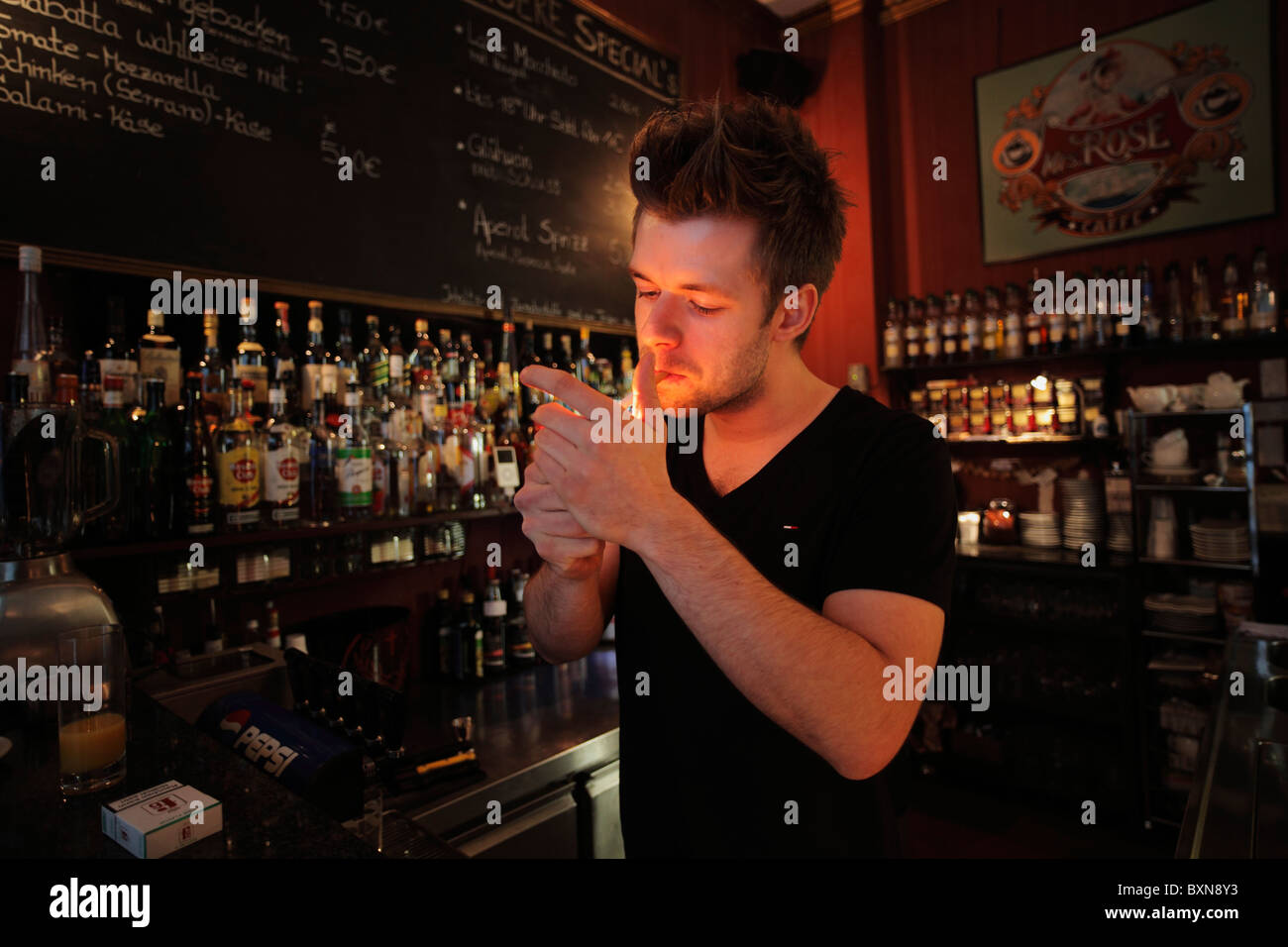 young barman lighting a cigarette behind the counter in a bar - Stock Image