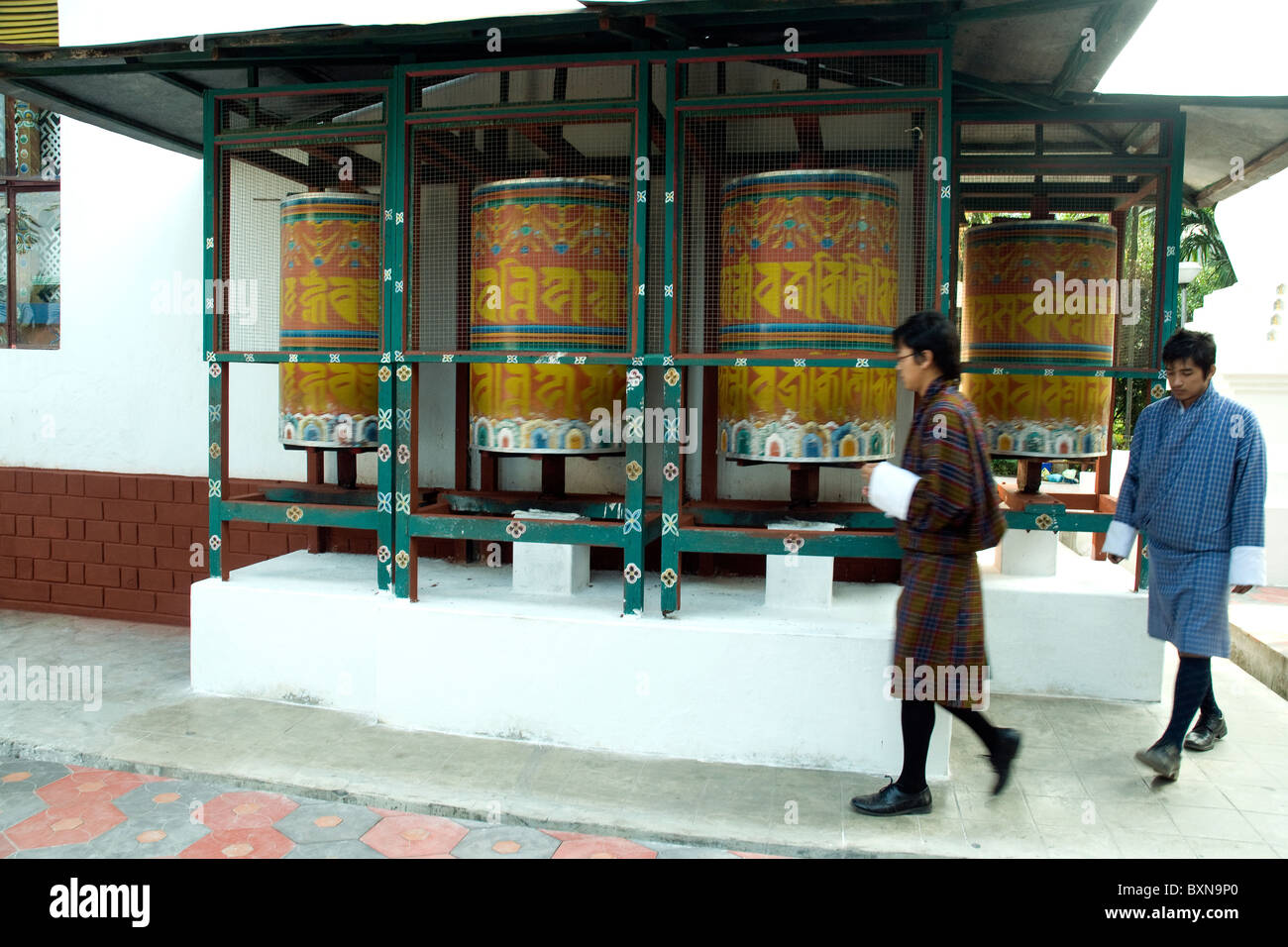 Ar the Kharbandi monastery near Phuntsholing, Bhutan, two young men  in national dress approach sacred prayer wheels - Stock Image