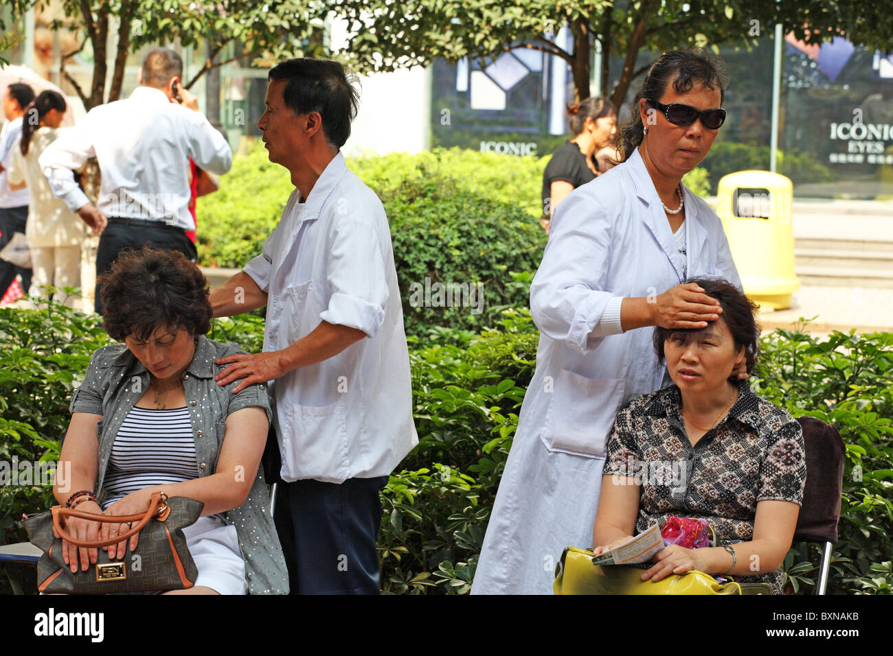 Blind Masseuses massage patients on streets of Kunming, China Stock Photo