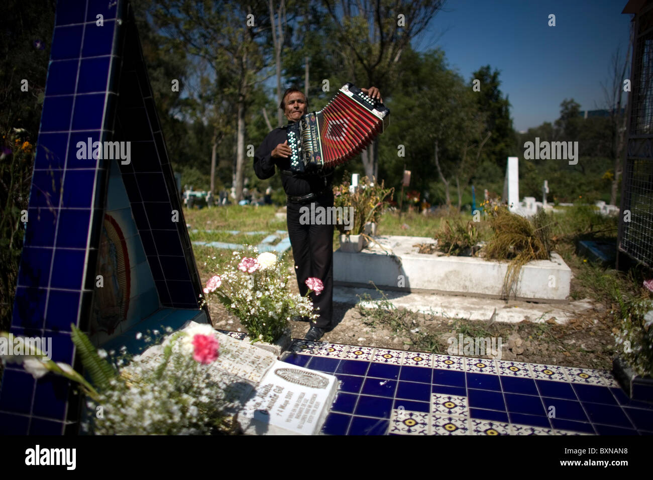 An accordion player waits for customers to hire him to play at grave sites in the Dolores cemetery in Mexico City - Stock Image