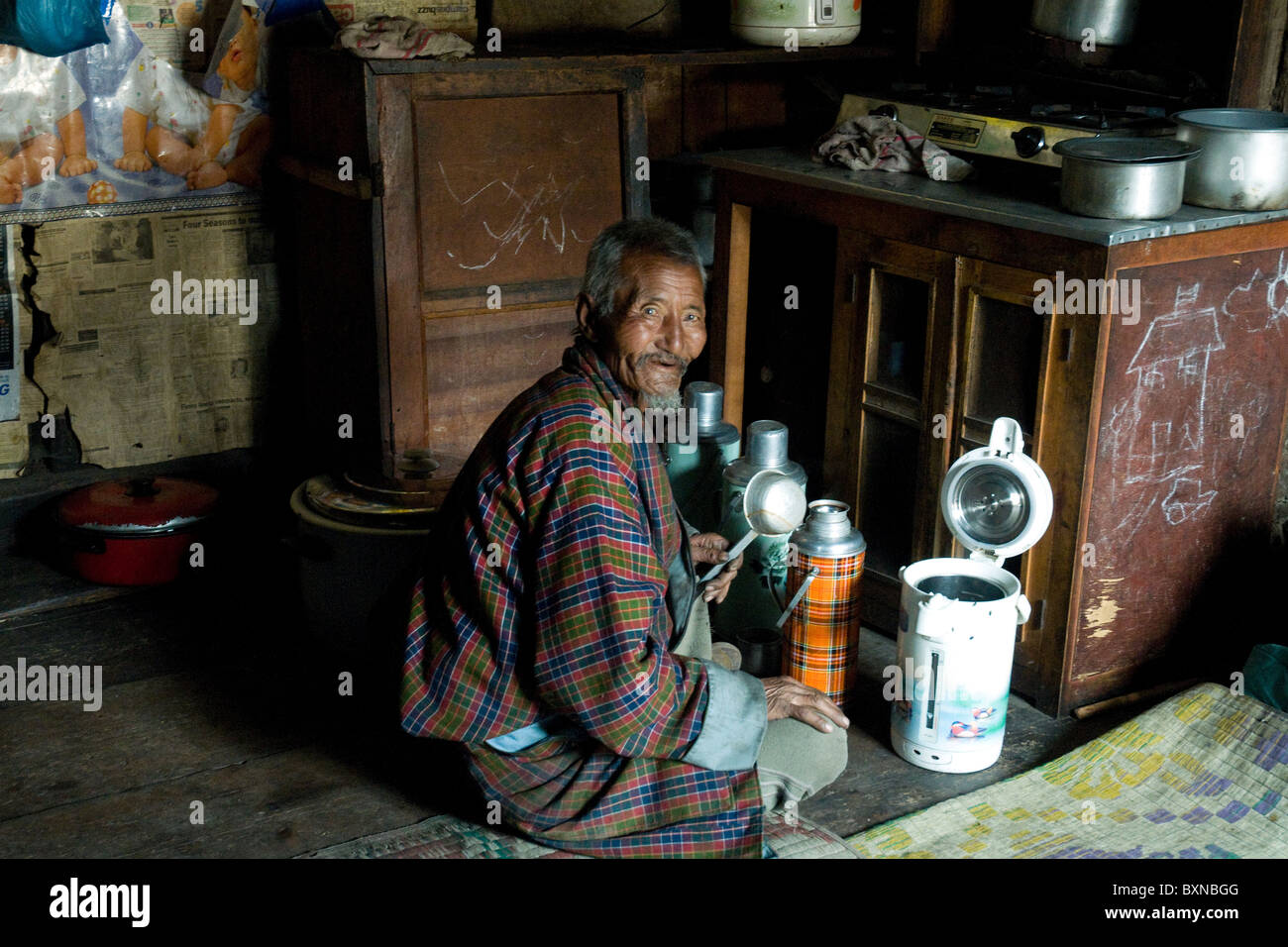 In the kitchen of his farmhouse home in Bhutan the family patriarch prepares a thermos of tea - Stock Image