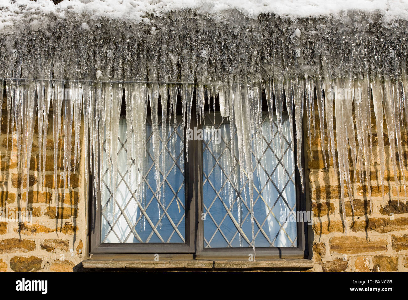 A Cottage with Giant Icicles on it - Stock Image