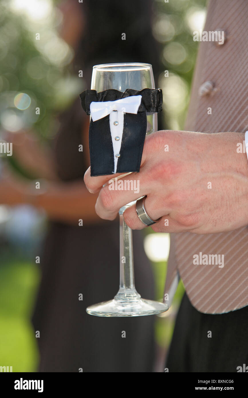 modern groom holding grooms champagne flute during wedding toast - Stock Image