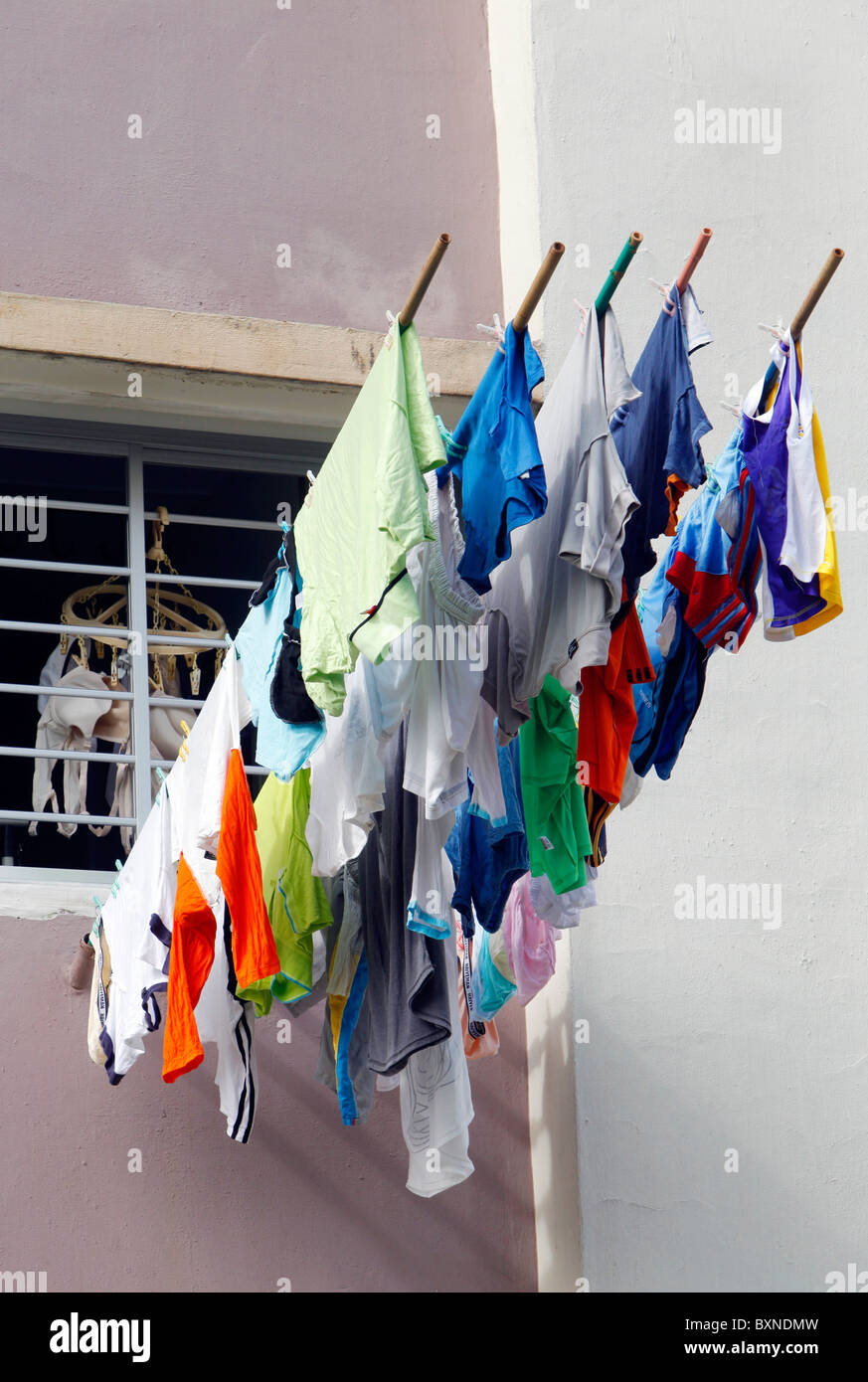 Singapore, the washing is hung out of the window to dry on a stick - Stock Image