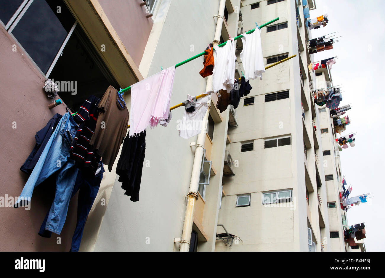 Singapore, the washing is often hung out of the window to dry on a stick - Stock Image
