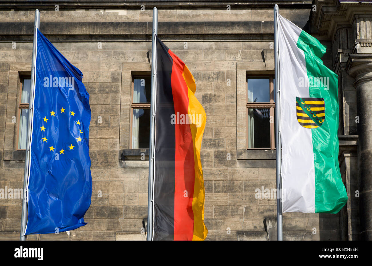 GERMANY Saxony Dresden Fags of EU European Union Germany and Saxony flying on flagpoles in front of Neues Standehaus - Stock Image