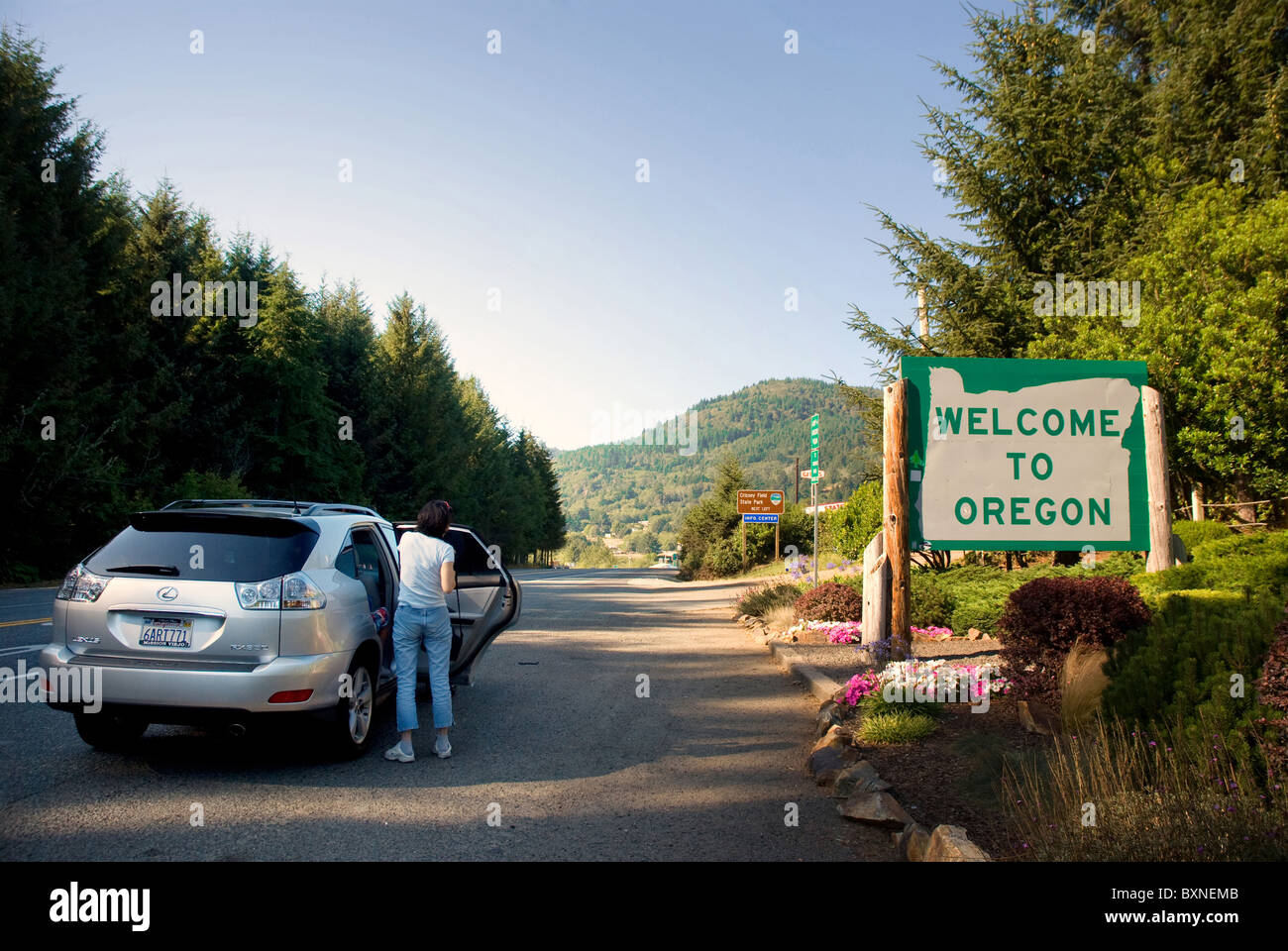 Travelers stopped at Welcome to Oregon sign on Highway 101 Stock Photo