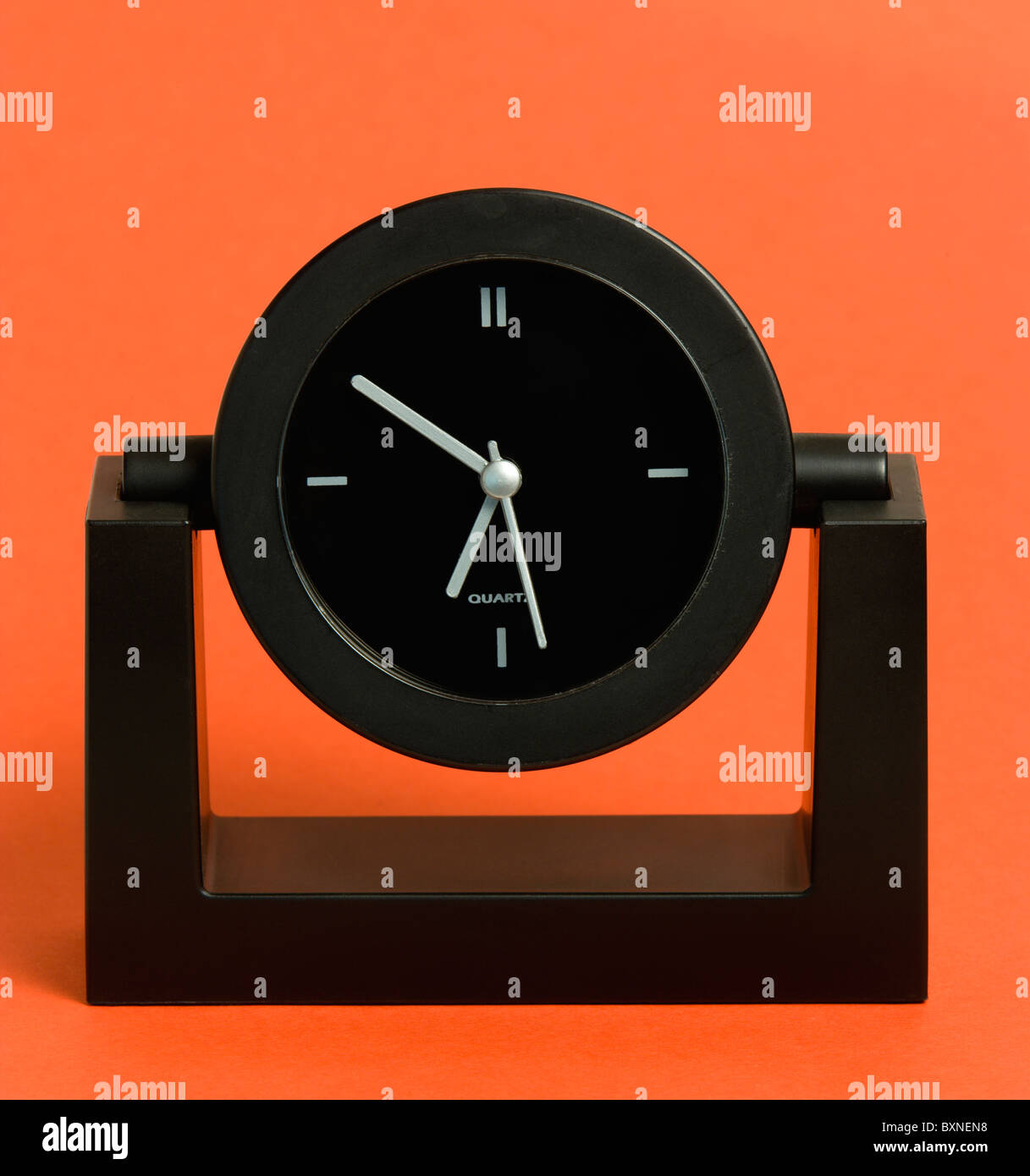 Time, Clocks, Analogue, Battery powered black analogue quartz table or desk clock against a red background. - Stock Image