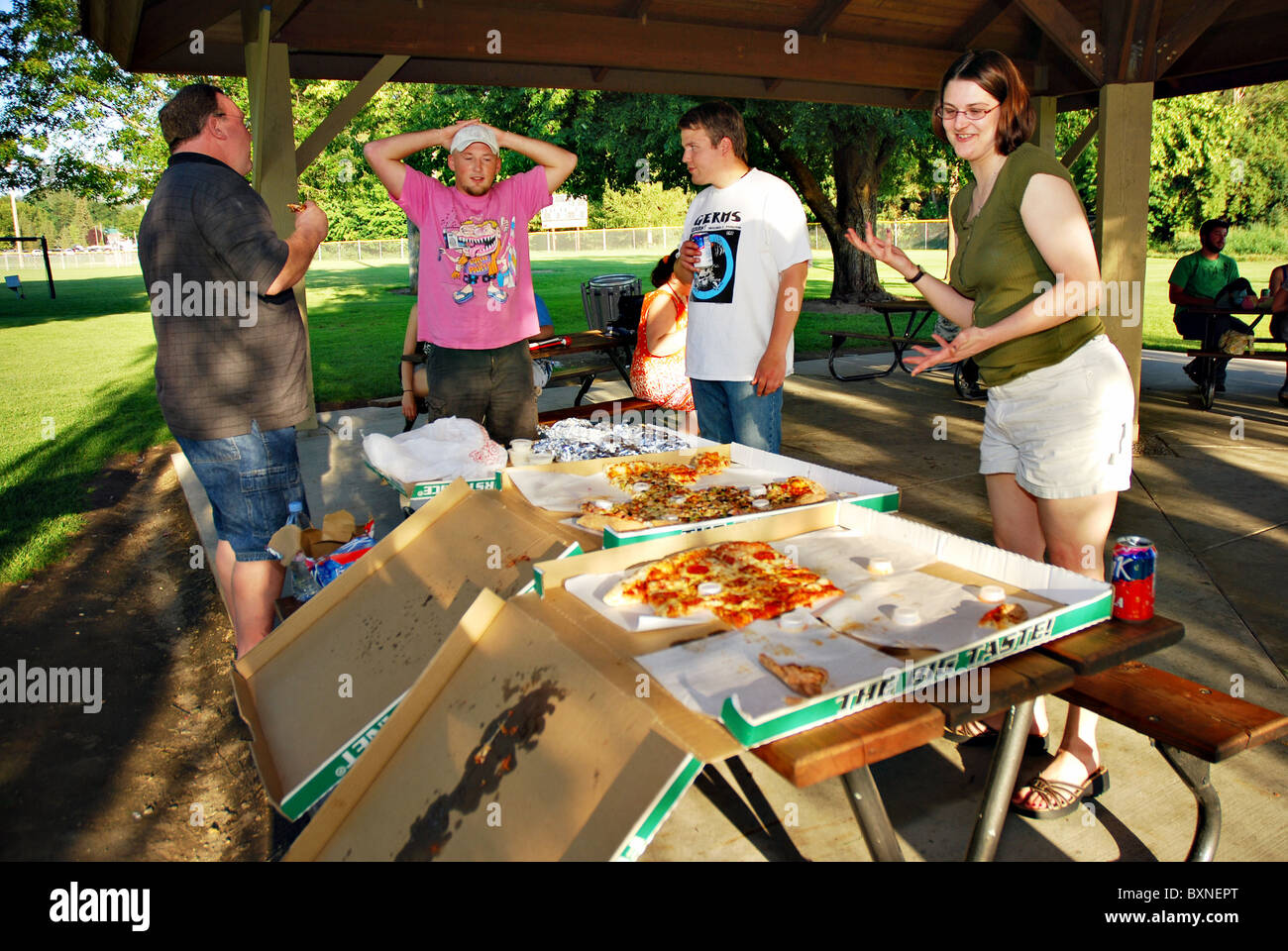 Adults having a pizza party at a park Stock Photo