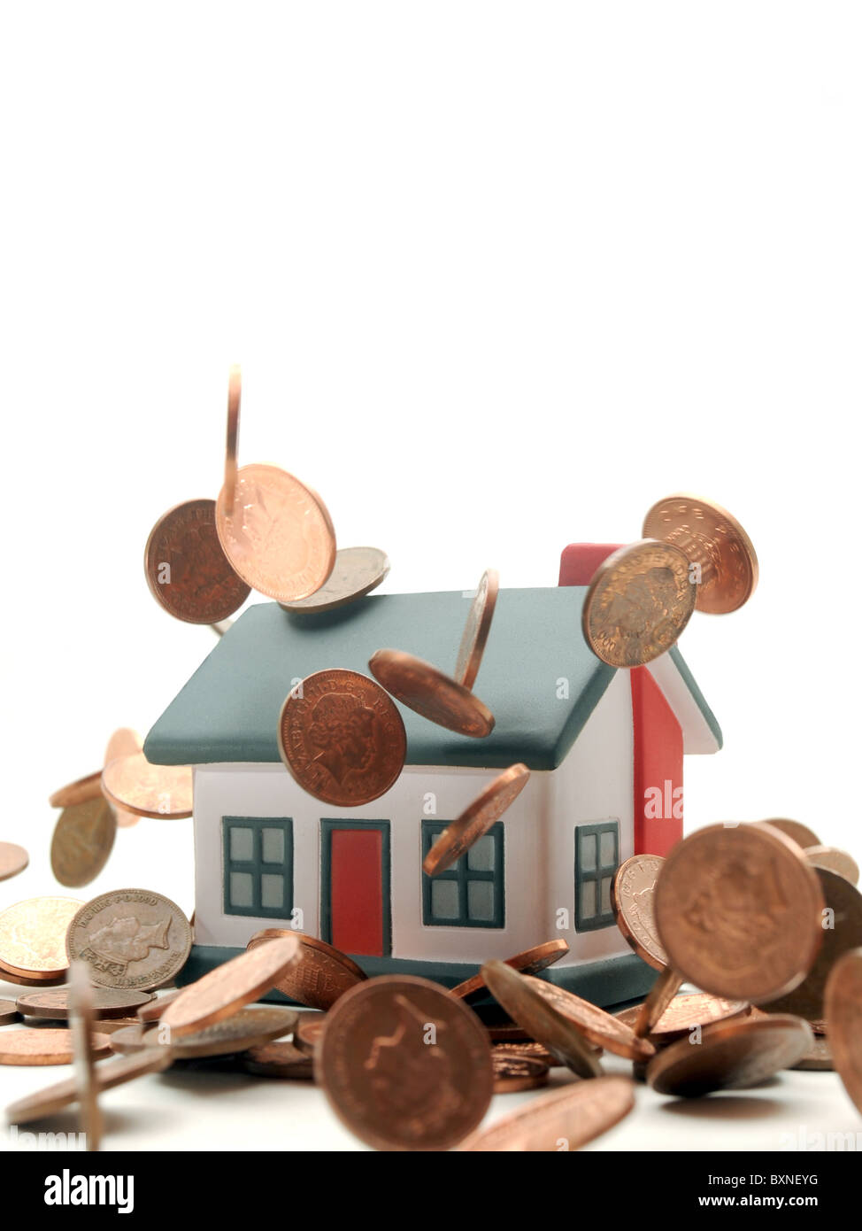 HOUSE WITH COINS DROPPING OVER IT RE PROPERTY MARKETS HOUSING COST BILLS  PRICES MORTGAGES FIRST TIME BUYERS ETC - Stock Image