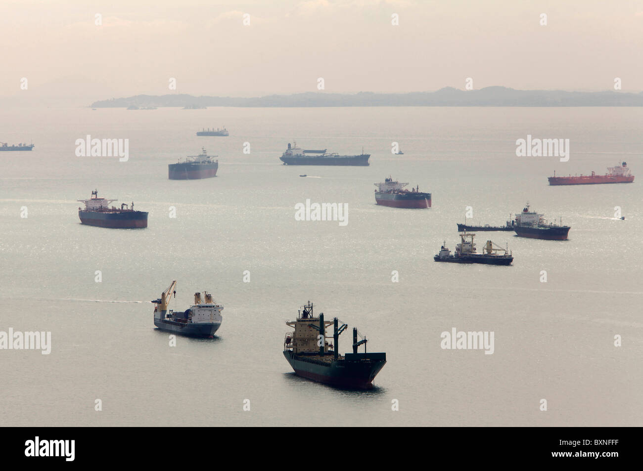 Ships waiting off shore of Singapore harbor, waiting to dock - Stock Image