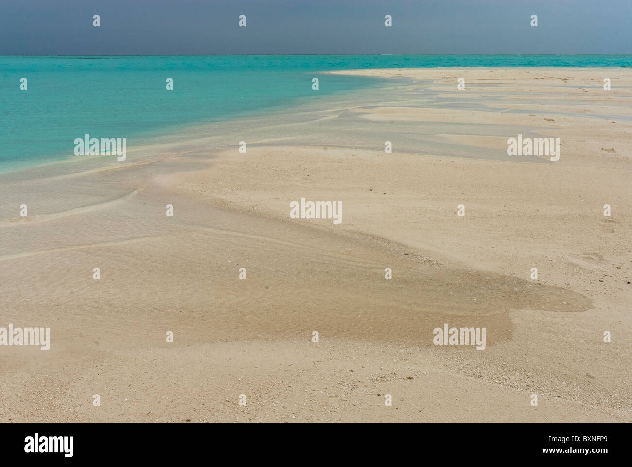 Sandbar next to a turquoise tropical sea under a dark stormy sky. Maldives, Indian Ocean. - Stock Image